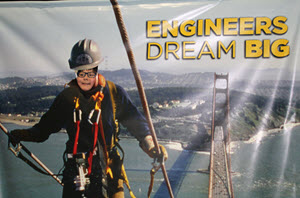 A girl pokes her head through for a picture as a Golden Gate Bridge climber at ASCE's Dream Big movie display.