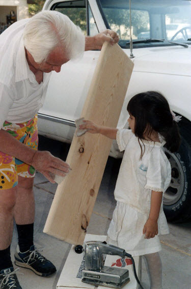 Yung Koprowski helps her father sand shelves.