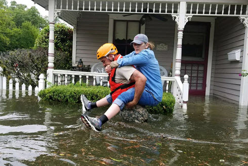 A Texas National Guardsman carries a resident from her flooded home.