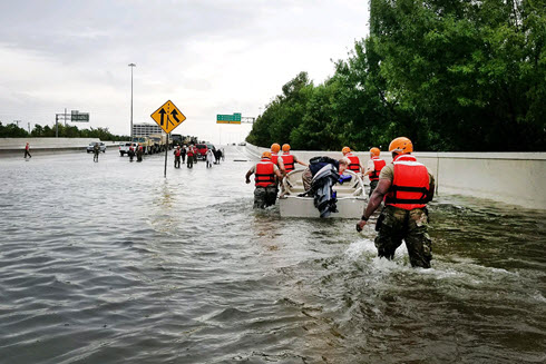 Texas National Guardsmen rescue a resident by boat.