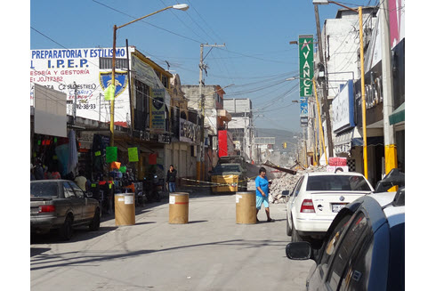 Repair and demolition work coexists with shops open for business in Jojutla.