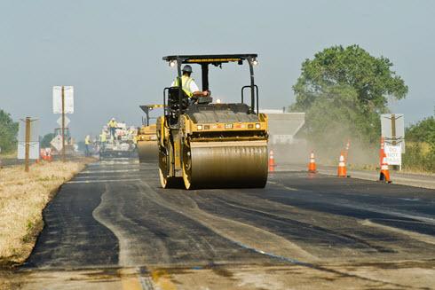 Man on construction paving vehicle.