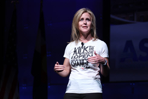 Woman standing and wearing a T-shirt saying kick open the door