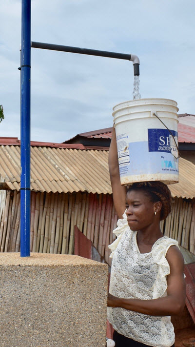 photo of woman filling bucket with water