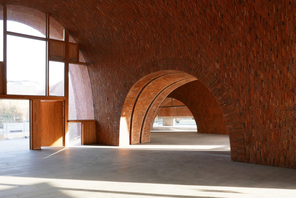 arched openings in a series of brick rooms with curved ceilings
