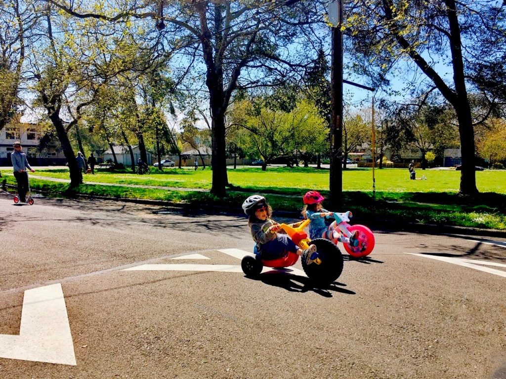 two children ride big wheels past a park on a sunny day