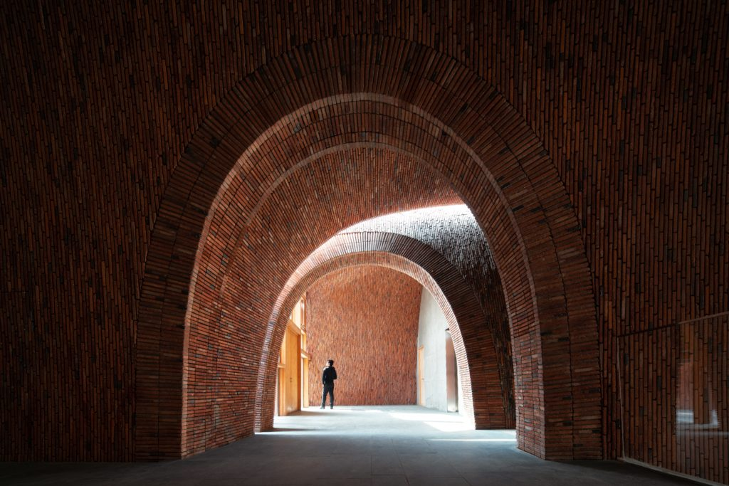 a long narrow walkway pierces through multiple brick buildings with curved archways.