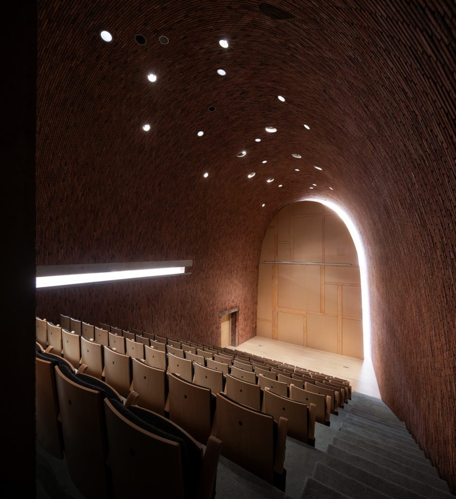 stadium seating looking at a stage in a brick room with a curved ceiling