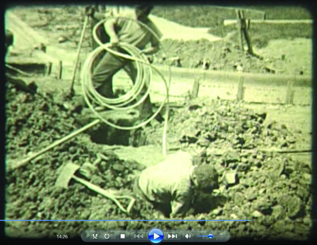 frame from a 1938 film showing workers installing a copper service line