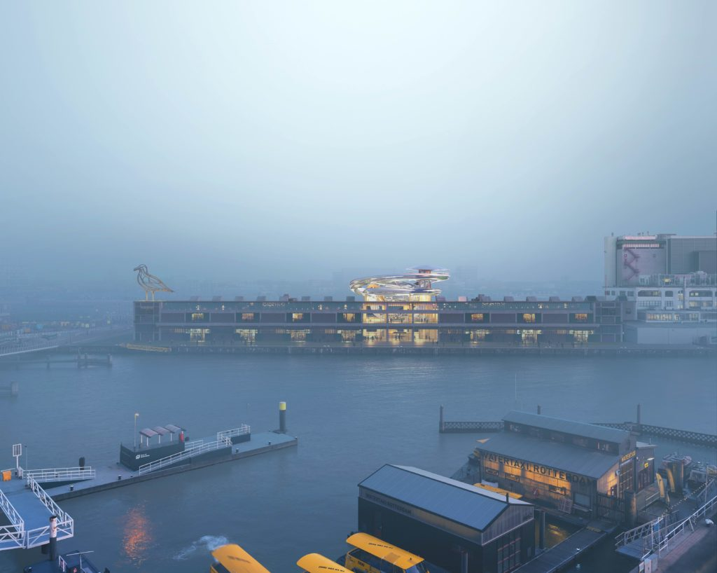 a warehouse on the waterside is visible through the mist at dusk