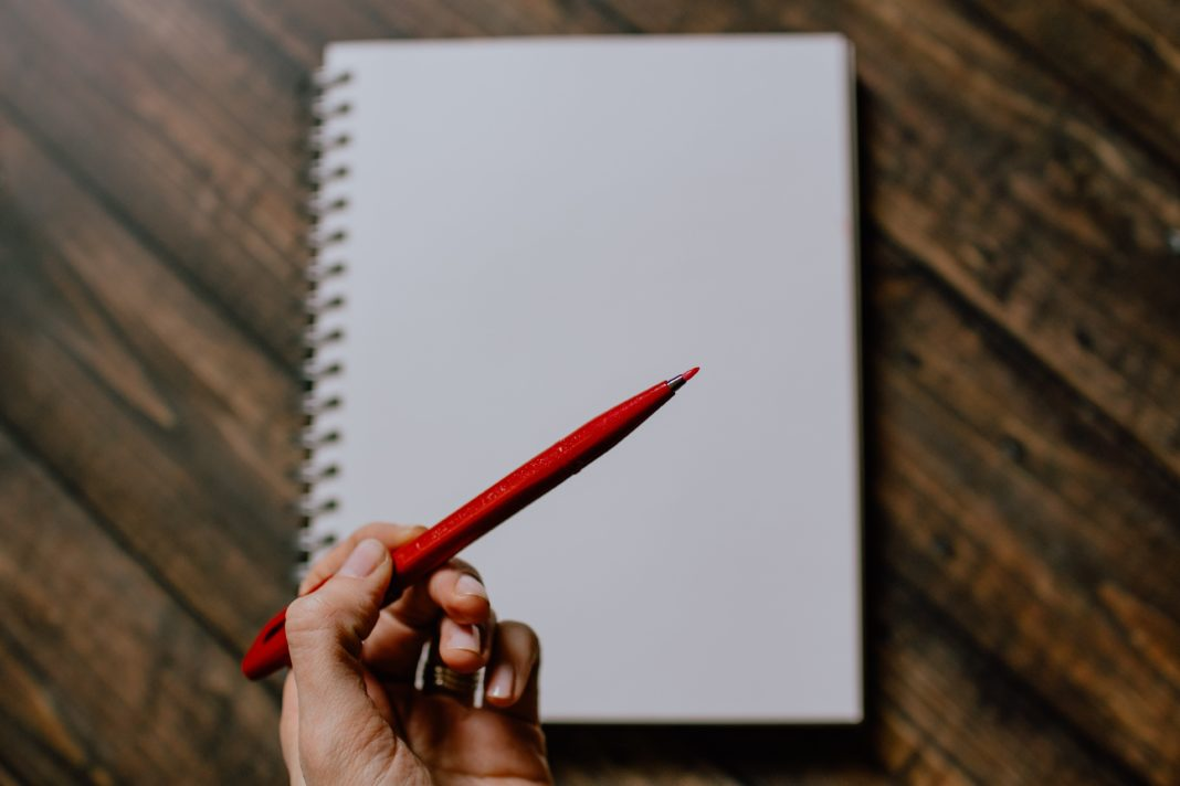 editor's note icon showing blank notebook and someone holding a red pen