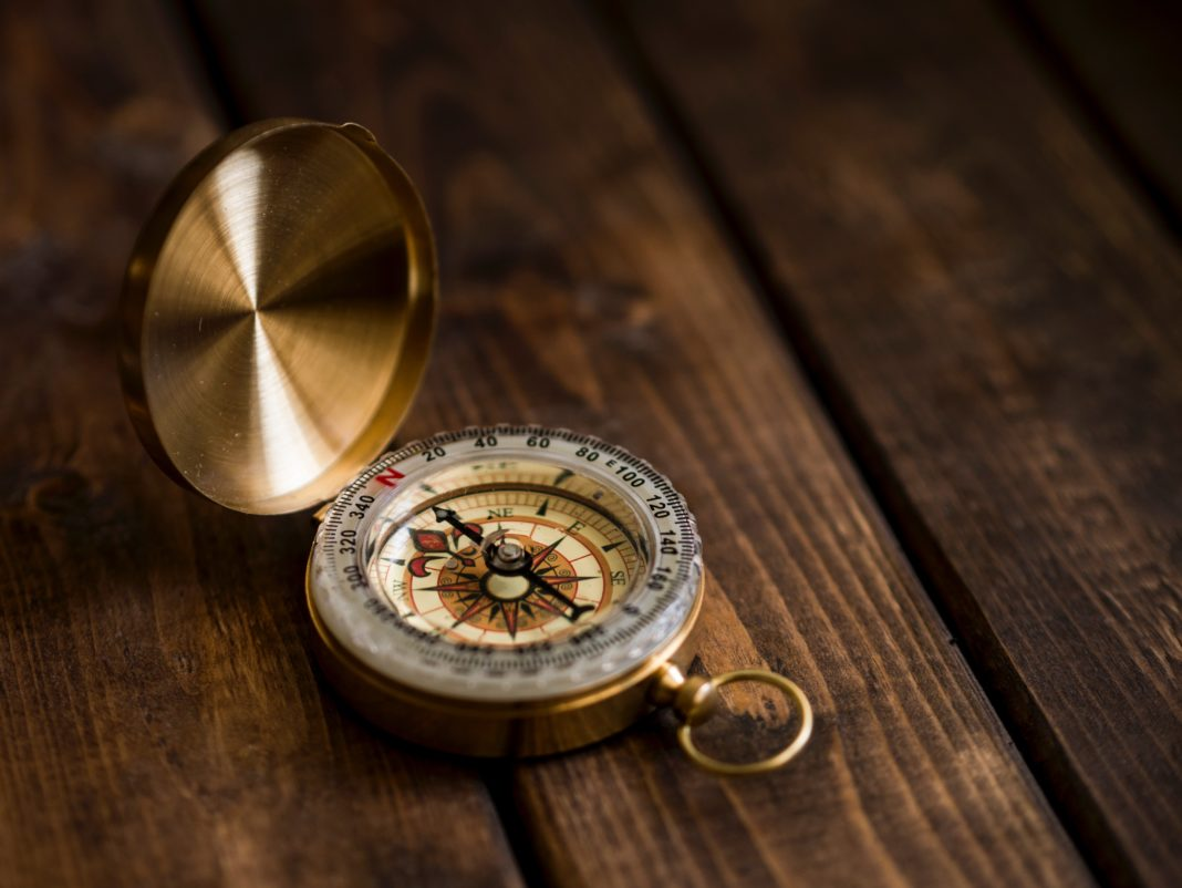 open compass on dark wood table