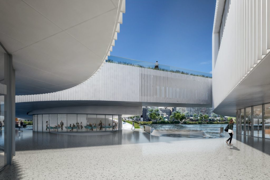 looking at the water from within a plaza with white curving rooflines and glass encased rooms visible