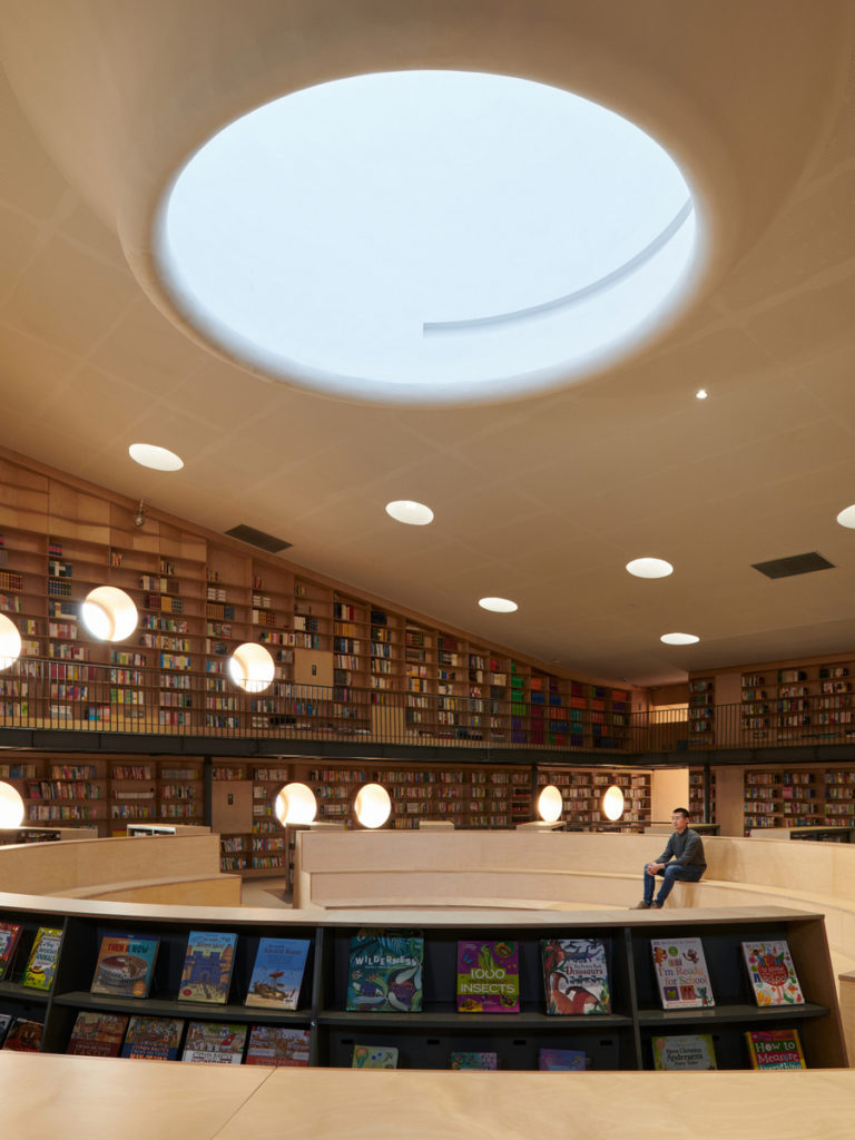 a look up at a oculus in the ceiling of a wood-paneled library with many books