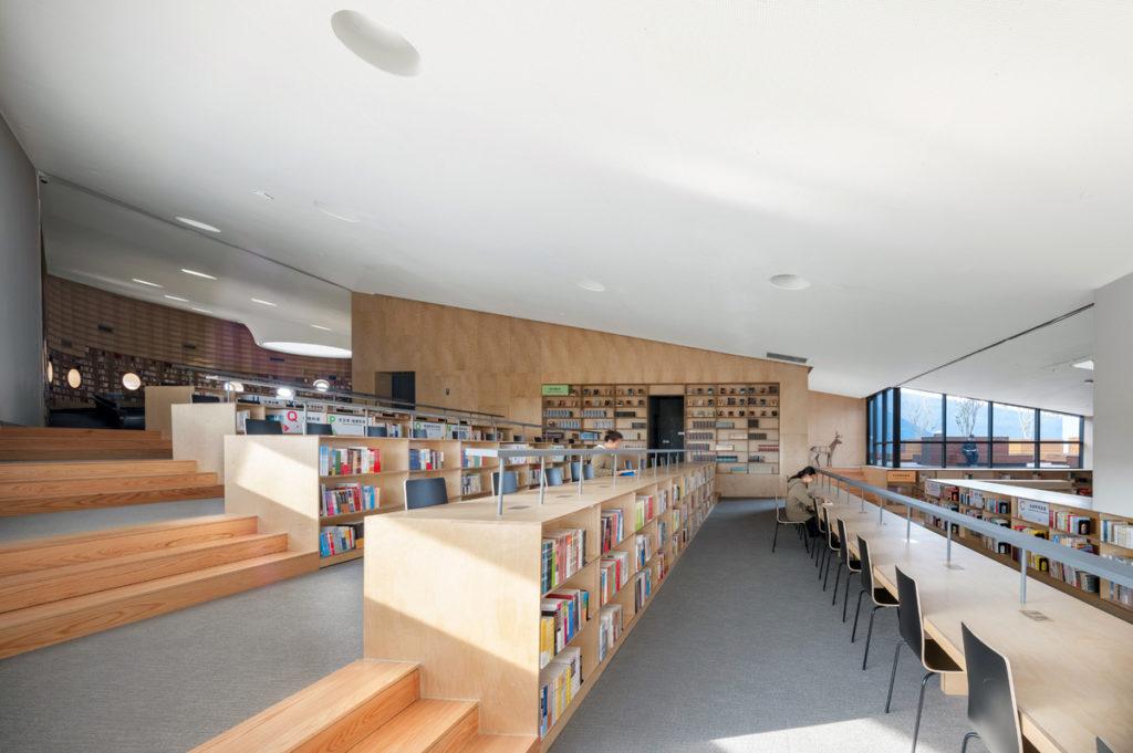 five terraced levels of low bookshelves facing long wooden desks, drenched in natural light