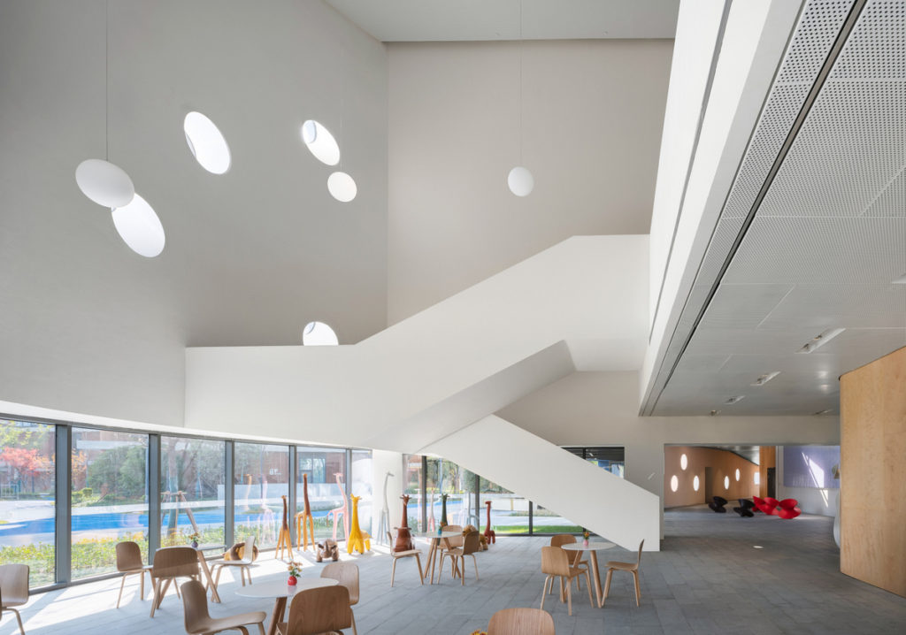 a large open room with wooden cafe tables and chairs and a white stairway accessing an upper balcony
