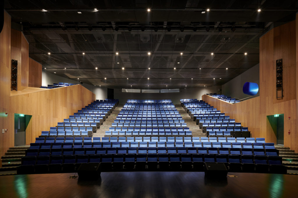 standing on a stage, looking at an auditorium of terraced blue seats