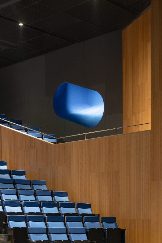 a close look at a small exterior porthole window next in an auditorium