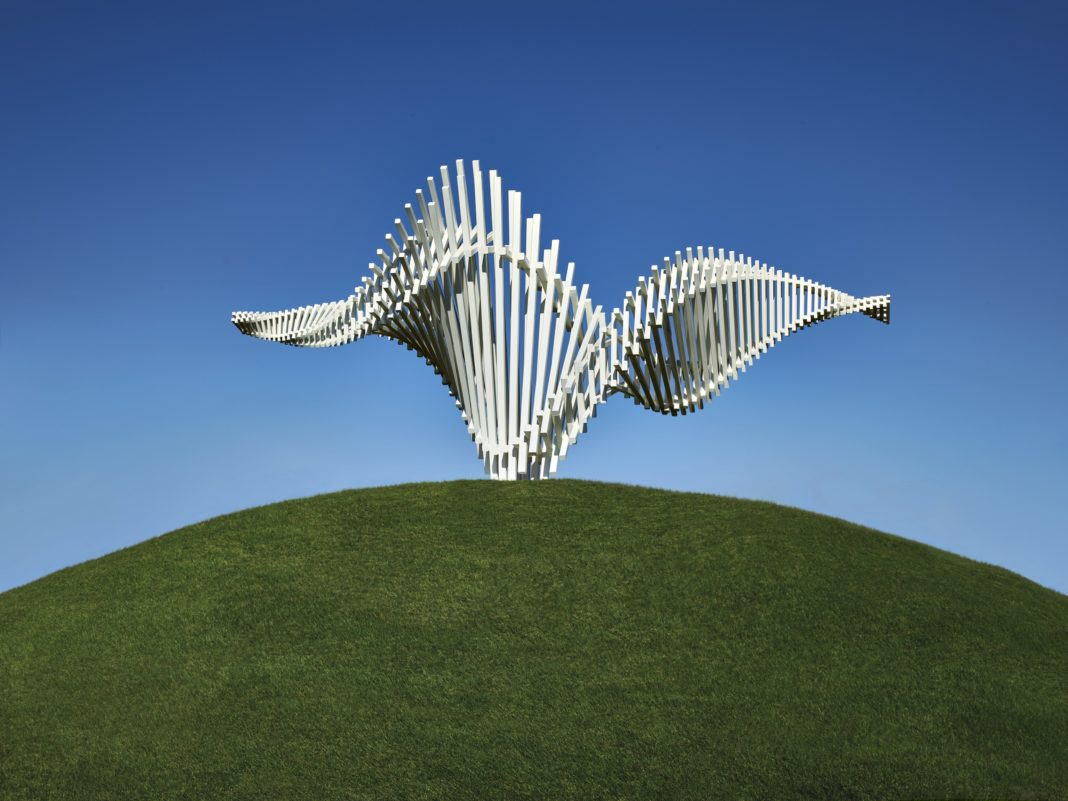 a horizontal, twisting sculpture formed of long, thin white bars on a green hill, against a blue sky