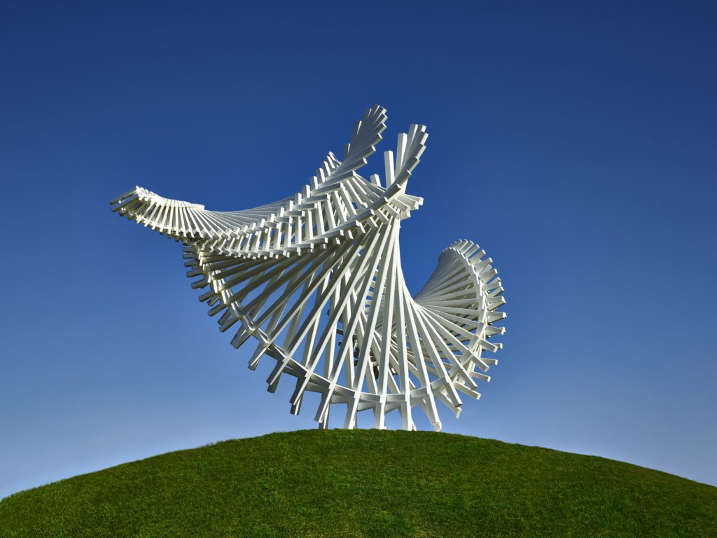 the sweeping side of a sculpture formed from connected long white bars against a blue sky