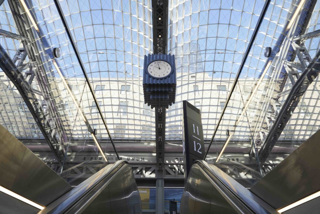 looking up at skylights and a clock from an escalator