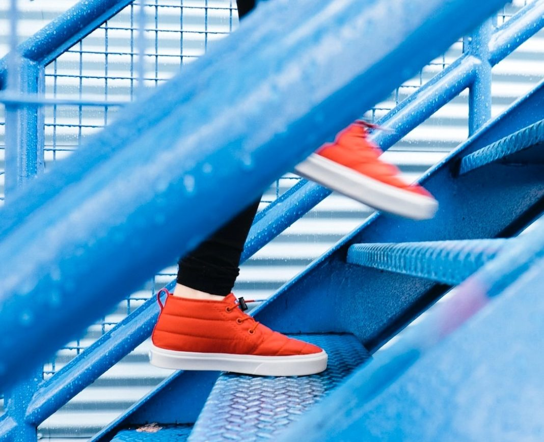 photo of person in orange sneakers walking up blue steps