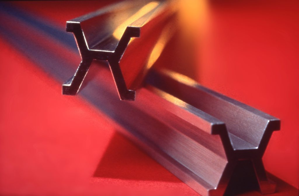 two crossed platinum-iridium bars against an orange background