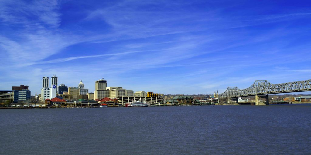 looking across a wide river at a low-rise city skyline on a bright blue day