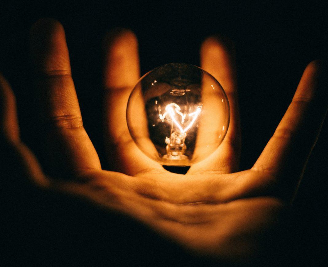 light bulb hovering over hand