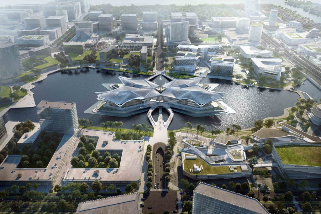 aerial shot of a star-shaped building located in a lake with a four-lane road that extends underneath the building and lake