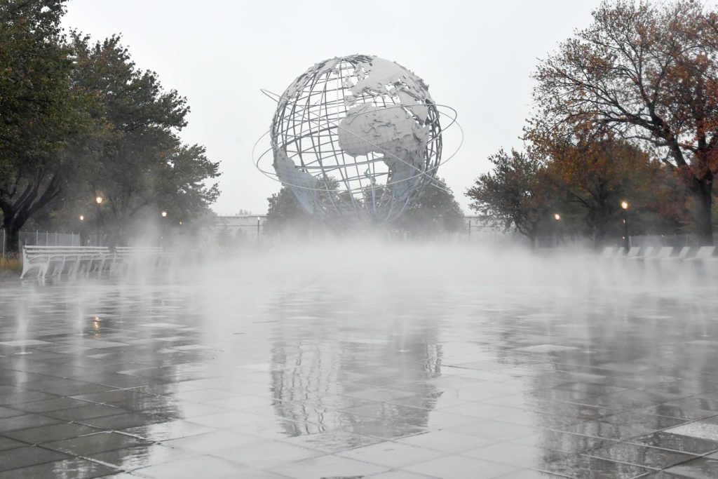 looking at a stainless steel globe sculpture on a gray day while artificial fog rises above a refurbished reflecting pool