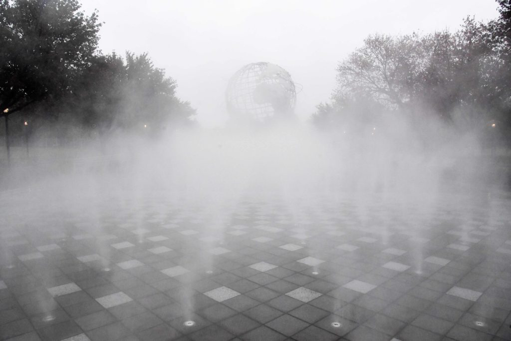 a thick layer of fog hides the Unisphere sculpture from site on a gray day