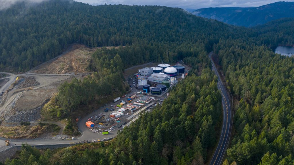 aerial shot of a treatment facility on a narrow site surrounded by hills and trees