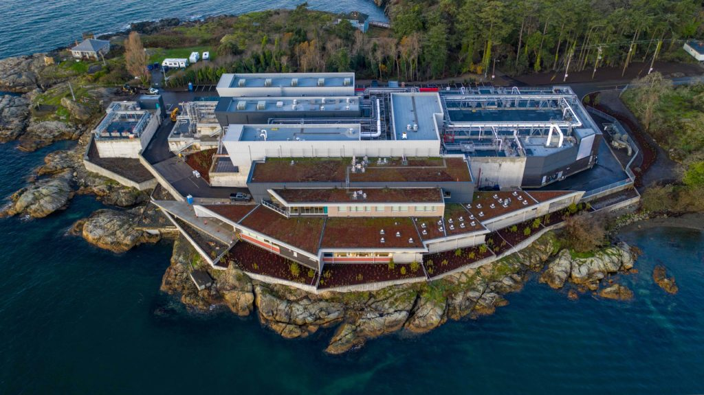 aerial shot of wastewater treatment plant with green roofs located on the waterside
