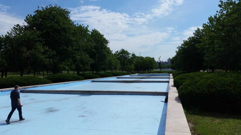 a man walks up the middle of an empty, stepped reflecting pool
