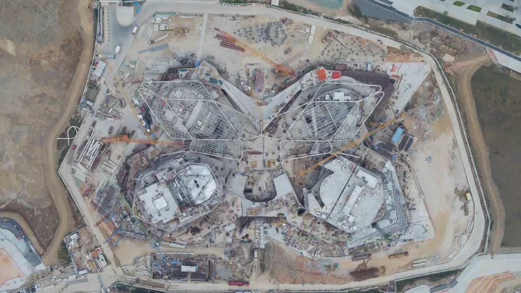 aerial shot of an under-construction site with four buildings and two steel canopy arms visible