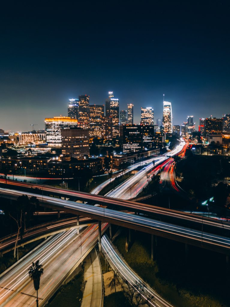 multiple stacked levels of freeways passing in multiple directions and angles at night