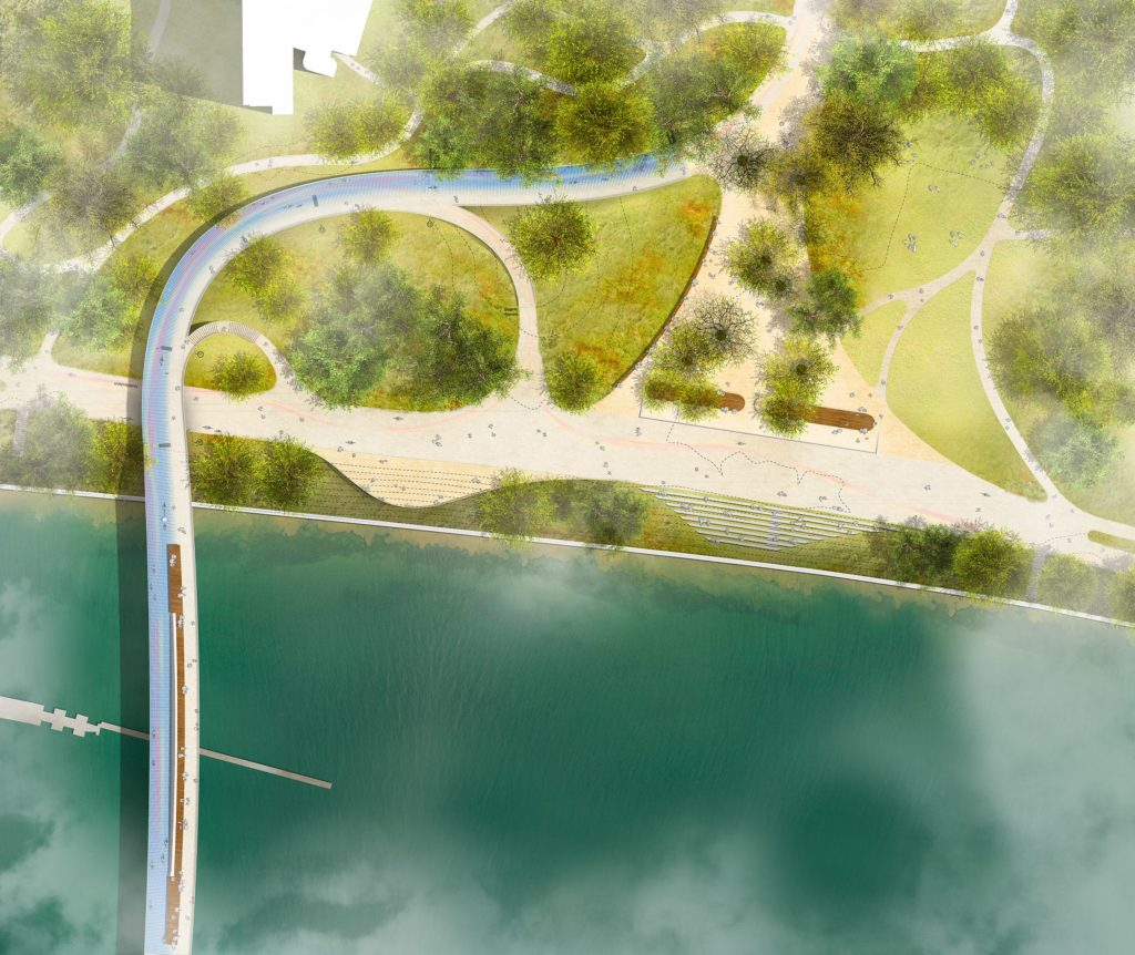 an aerial shot of a large sweeping curve of a bridge over green parkland next to a river