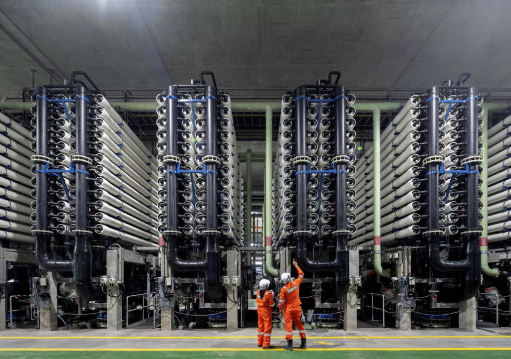 two workers in orange stand before a system of tubes that extends upwards of two to three stories in height