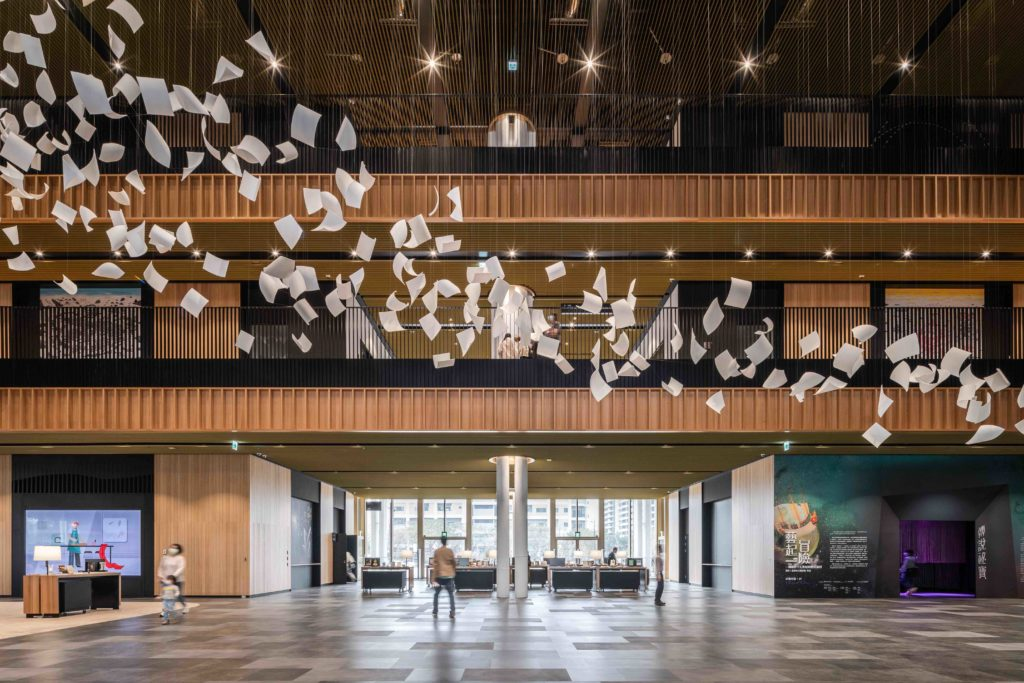 a double height atrium clad in wood, with an art installation that looks like pieces of white paper blowing in the wind