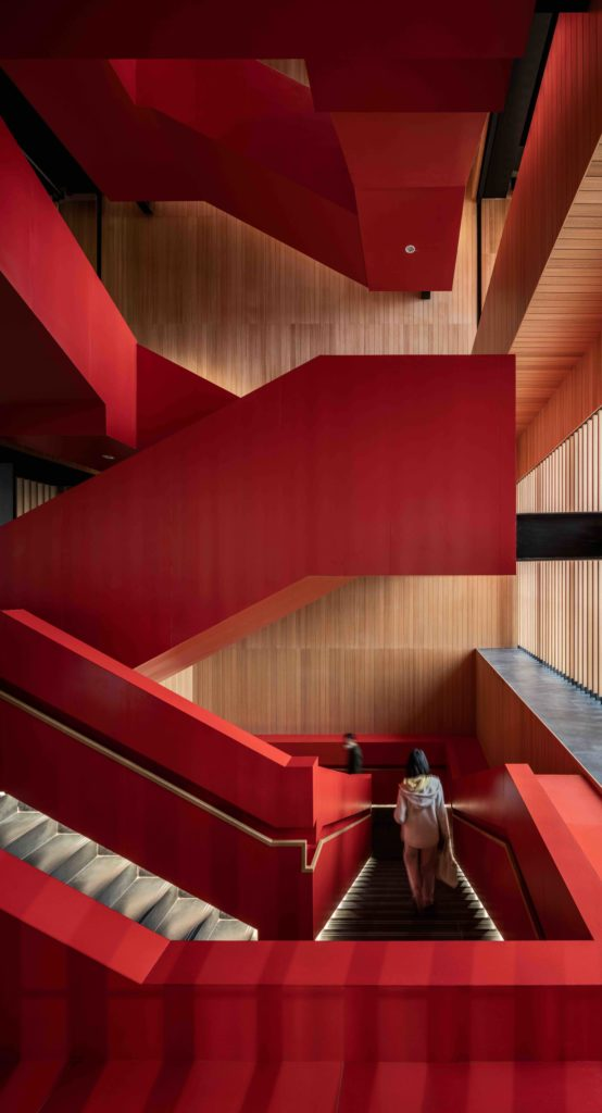 a striking red, open-air interior stairway with a person walking on the landing