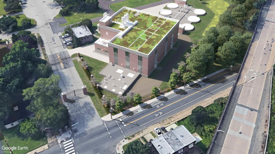 aerial shot of a multistory brick building with a green roof, located at an intersection