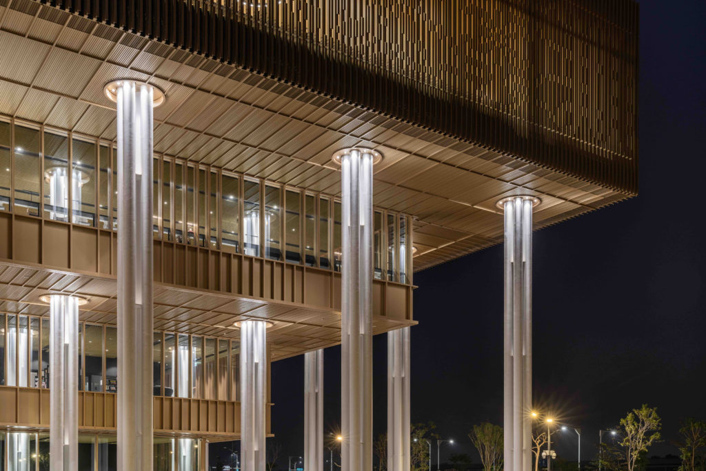 a close look at the corner of a building, glowing from within at night, with delicate columns and facade detailing