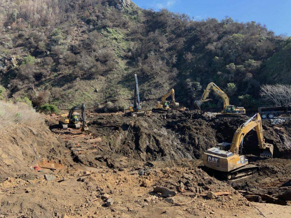 excavators remove debris from a dirt site