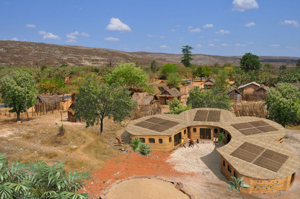 looking down on four huts linked together in a semicircle located amidst sand and trees