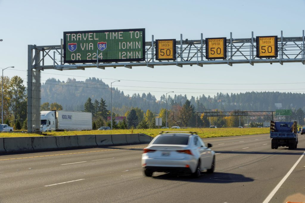 a silver car travels along a highway under smart boards that display expected travel times
