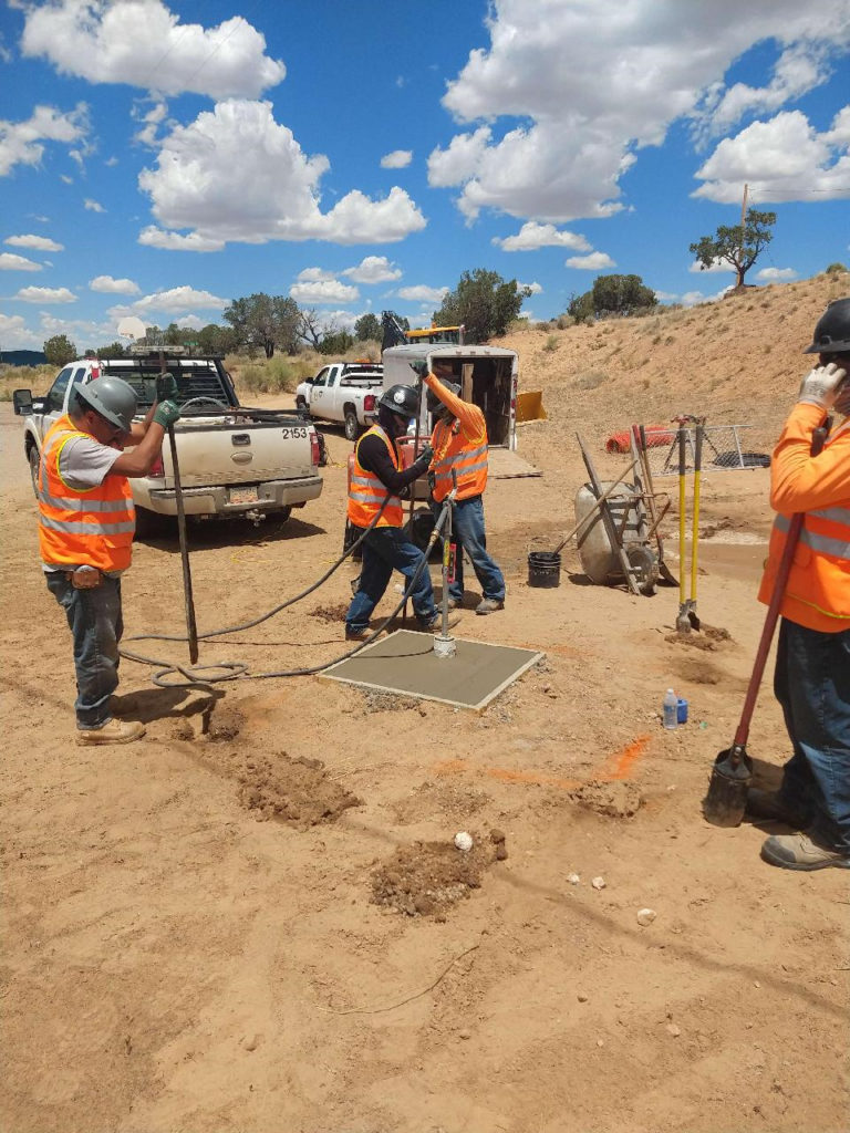 construction workers in orange vests surround a small concrete pad in desert terrain