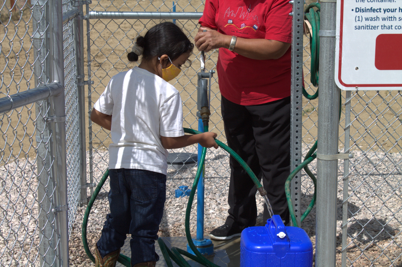 a child fills a personal container with clean water from a hose attached to a short vertical pipe located within a chain link enclosure