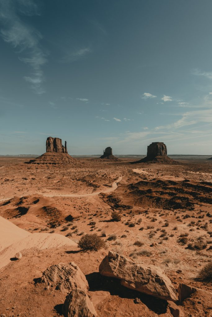 a vertical image looking at the arid terrain and rock piles of Monument Valley