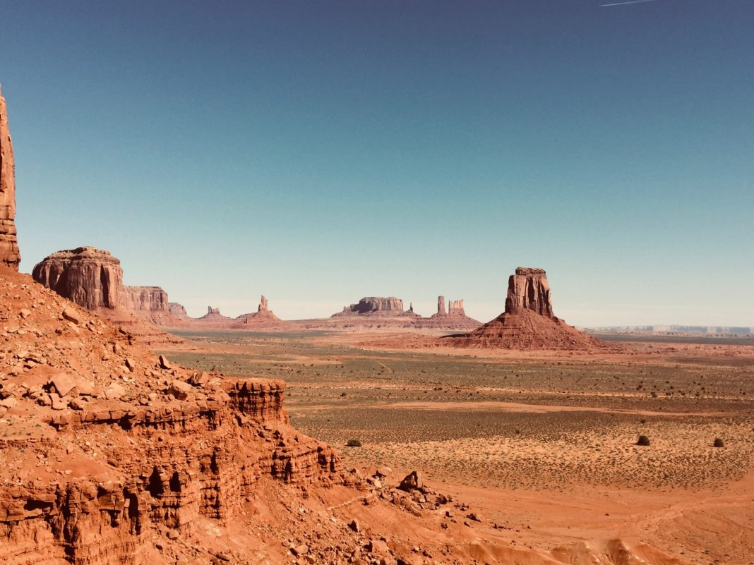 looking across a beautiful arid valley with rock formations standing tall against a blue sky